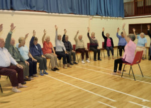 Group of older people taking part in exercise class at landford village hall